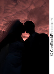 Kissing - Couple kissing silhouetted against colourful sky...