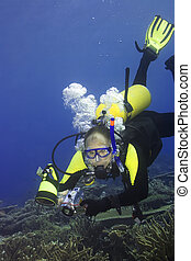Diver with camera in deep and bubbles.