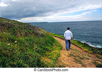 Brittany coast - A man walking on a hiking trail along the...