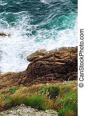 Brittany coast - Looking down a cliff onto stormy ocean at...