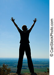 Hands free - Woman on the top of a mountain happy