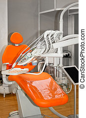 Dentist chair - Orange dentist chair with bunch of equipment...