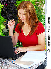 Woman working at home - Happy mature woman working on a...