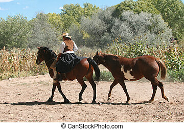 Cowgirl on a Dusty Road - Cowgirl dressed in traditional...