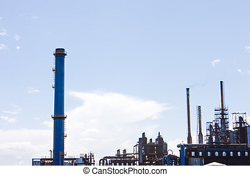 Factory with smoke stacks against blue sky