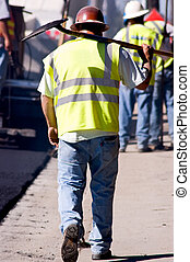 Weary - A tired paving worker walking down the street,...
