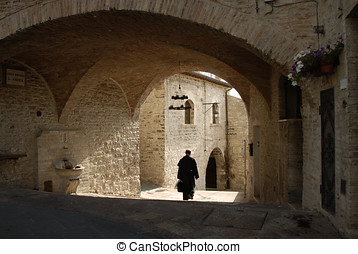 Assisi, Italy - a priest walks along a street in Assisi,...