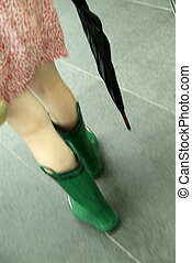 woman in waterproof wellington boot - woman walks in short...