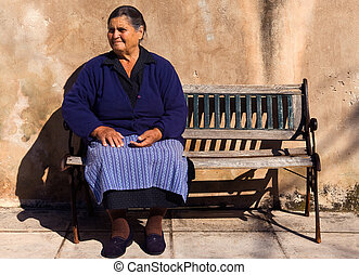 Old lady in a Greek village - Picture of an old lady sitting...