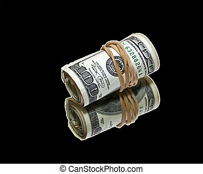 money on black - roll of money wrapped with an elastic on a...