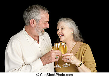 Champagne and Laughter - Good looking mature couple laughing...