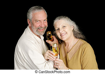 Intimate Champagne Toast - Happy mature couple toasting...