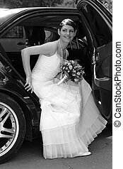 Portrait of a bride getting out of her wedding car limousine...