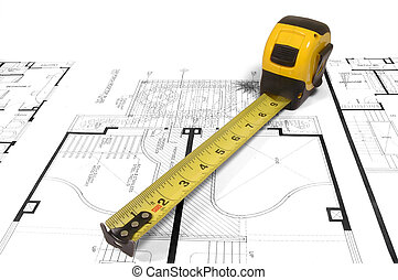 Home Plan - A measuring tape over a construction drawing of...