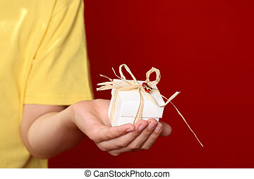 Giving a gift - Hand offering a small decorated gift against...