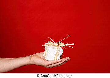 Giving a present - Child handing a small gift tied with...