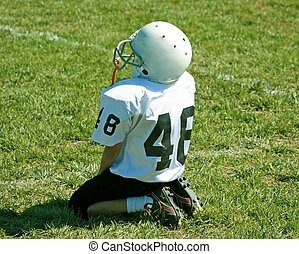 youth football - young football player wathches from the...