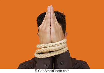 Captive men praying - A bussinessmen tiedup by his fists...