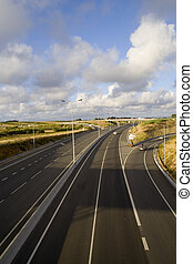 The highway - a perspective of a highway with a cloudscape...