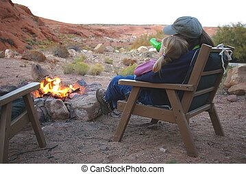 Campfire - A little girl drinking hot chocolate by the...