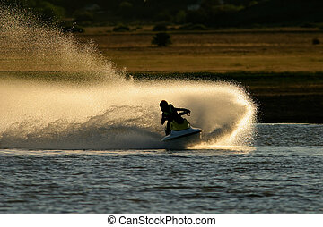 Jet ski action - Backlit jet ski with water spray, late...
