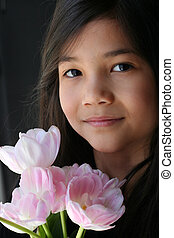 Child with pink tulips - Girl holding a bouquet of pink...