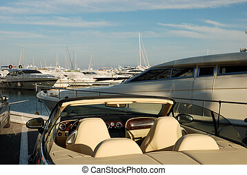 Luxury car and yachts in the harbor of Marbella, Spain