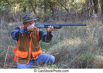 Kneeling Hunter Shooting - Hunter kneeling, aiming, and...