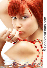 redhead with red beads looking over shoulder in water -...