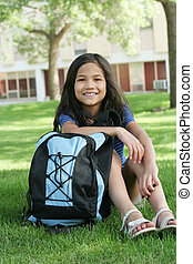 Child ready for school - Eight years old girl sitting with...