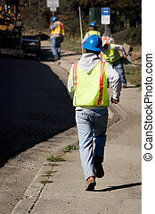 Catching Up - A worker on an asphalt crew running to catch...