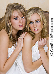 Sharing the Bed - Two beautiful young women wrapped in a...