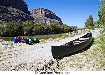 Canoe Trip End - A canoe and gear resting quietly beside a...