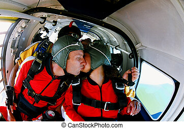 Two Skydivers kissing in an aeroplane - Two people pictured...