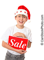Christmas Sale - Smiling joyful child holding a Sale Sign -...