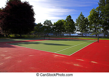 tennis court - wide angle of colorful tennis court over blue...