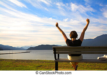 arms up - woman with her arms up over blue sky