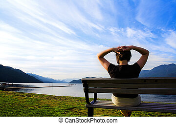 arms up - woman with her arms up over blue sky on a bench