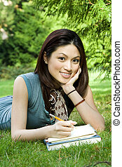 Studying girl - A beautiful college student studying outdoor...