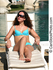 Beautiful model in solar glasses and blue bikini in a chaise...