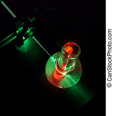 ruby rod under laser - a rod of artificial ruby immersed...