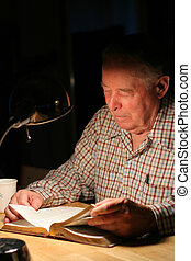 Elderly man reading Bible