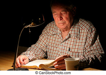Elderly man reading Bible by lamplight.