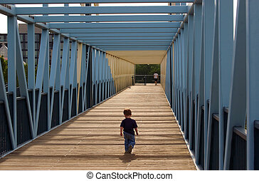 Boy on Bridge - lonely little boy walking on a bridge