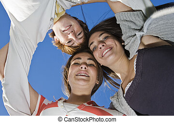 Teens - A group of caucasian teens holding onto each other...