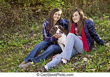Teens - Two caucasian female teens sitting in the park with...