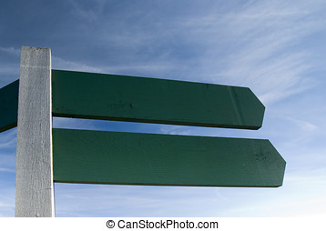 Sign Post - Blank wooden signpost against blue sky -...