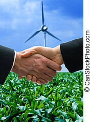 Energy deal - shaking hands with a wind mill in the...