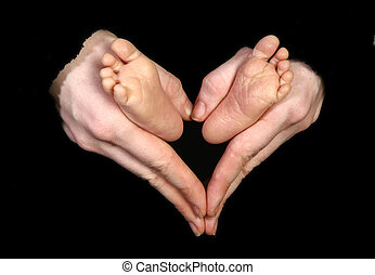 Baby Feet - Baby feet held by mothers hands making heart...