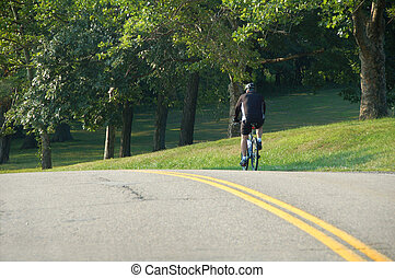 Biking - man riding bicycle on street with trees